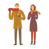 Pair wearing winter clothes holding hot coffee