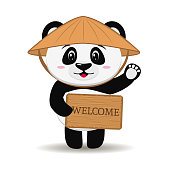 Panda in a hat in the style of a cartoon stands with his hand raised and holds a greeting sign.