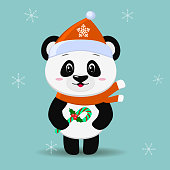 Panda in a red hat and scarf, in the style of a cartoon, stands with candy in his paw.
