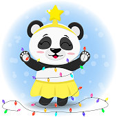 Panda in a yellow skirt and a star on his head is standing and holding a Christmas tree garland