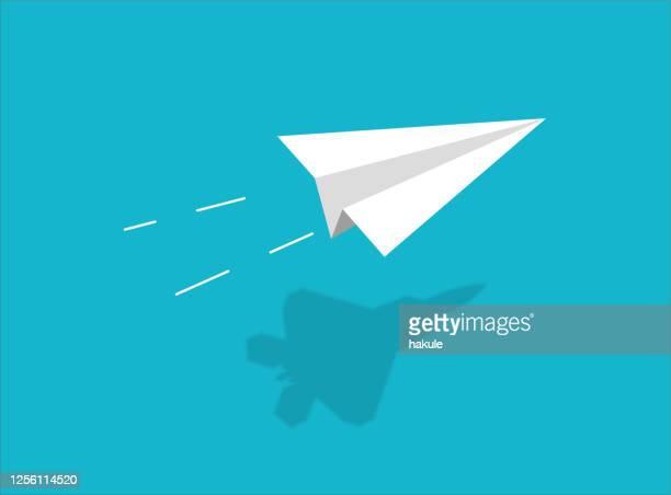 illustrazioni stock, clip art, cartoni animati e icone di tendenza di paper airplane with shadow of fighter plane - aeroplano di carta