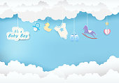 Paper art of cloud with toy shower on blue sky paper cut style, baby boy card illustration