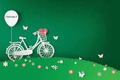 Paper art of Green background with bicycle in the field,eco,friendly,heart