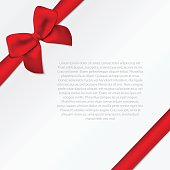 Paper card with diagonal ribbon and tied bow.