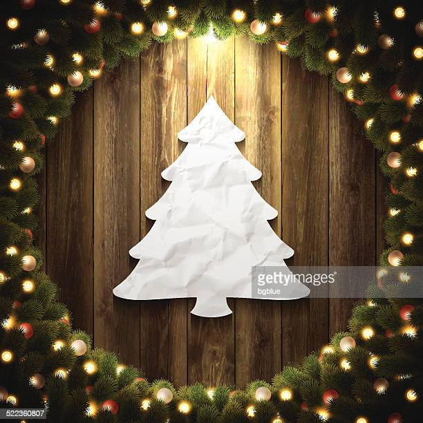 Paper Christmas Tree on Wooden Background with bright Christmas wreath