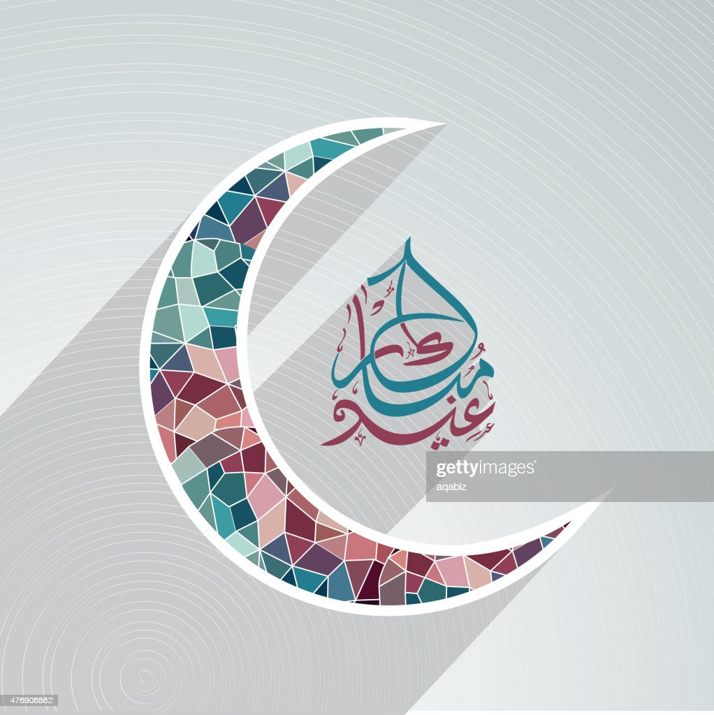Paper cutout moon with Arabic text for Eid Mubarak celebration.