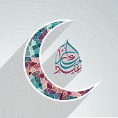 Paper cutout moon with Arabic text for Eid Mubarak celebration.