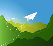 Paper plane flying pattern over  green mountain landscape.