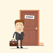 Pensive businessman or manager standing in front of a closed
