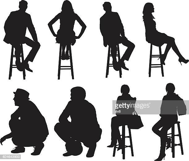 People sitting on stool and crouching