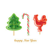 Peppermint candy canes. Christmas tree and rooster on stick