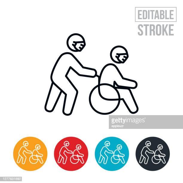 車椅子の人はフェイスマスク細い線アイコンを身に着けている介護者によって押されている - 編集可能なストローク - ホスピス点のイラスト素材/クリップアート素材/マンガ素材/アイコン素材