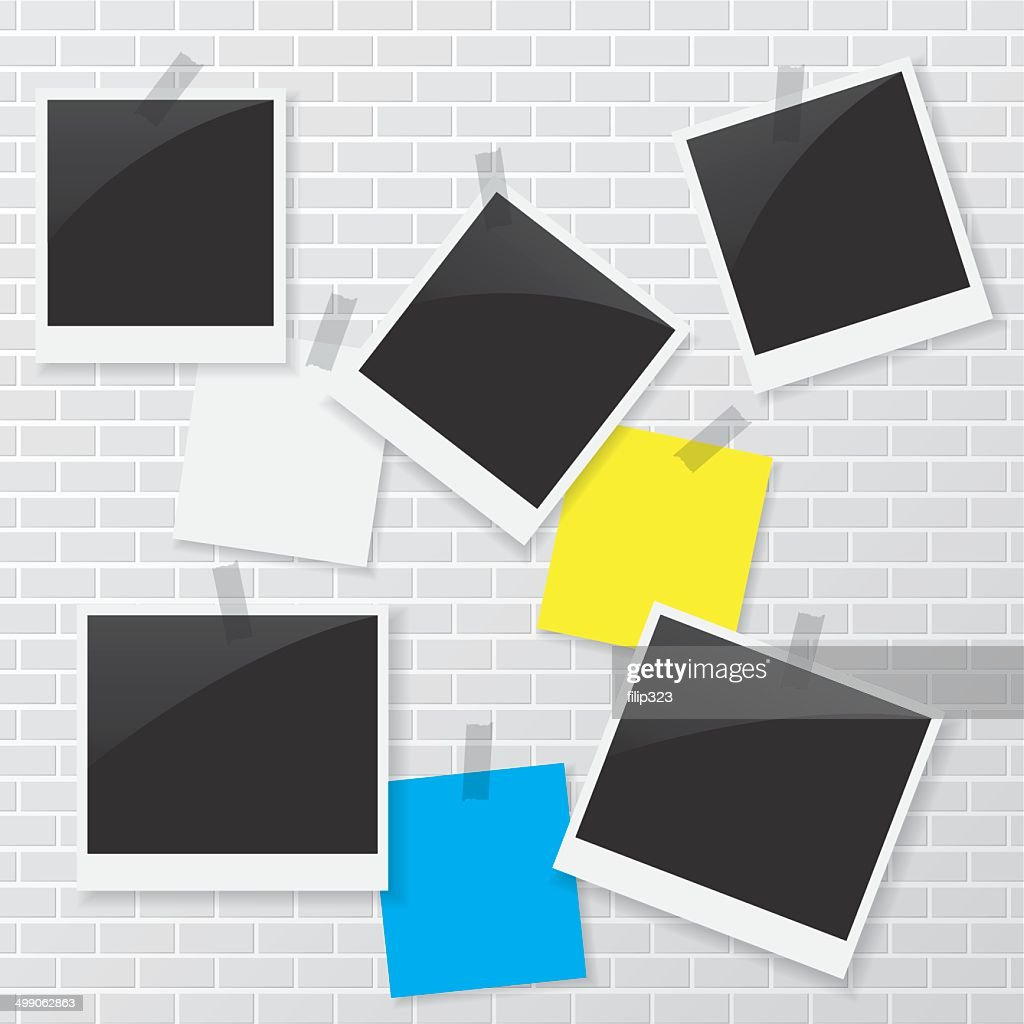Photo frame and blank paper on brick wall
