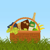 Picnic basket in a green grass. Wicker basket with champagne and food