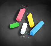 Pieces of chalk with shadow on blackboard background.