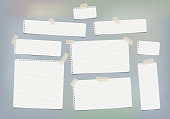 Pieces of white lined copybook, notebook sheets for note stuck with sticky tape gray background