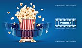 Popcorn for movie theater and cinema reel on blue background