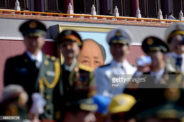 Portrait of Mao Zedong is seen as a group of Chinese military officers stand watching a military parade at Tiananmen Square to mark the 70th...