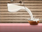 Pouring milk in clay bowl with splash, lot of drops standing on red checkered napkin on wood background, high quality realistic vector illustration