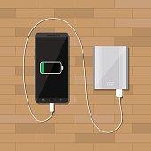 powerbank charging smartphone on wooden desk