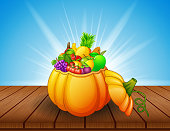 Pumpkin basket full of fruits and vegetables on wooden table