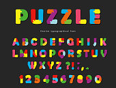 Puzzle font. ABC colorful creative letters and numbers on a black background.