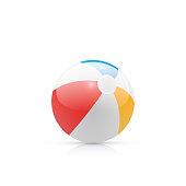 Rainbow colored beach ball on plain background