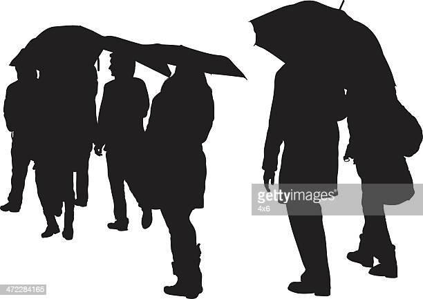 Regnerischen Tag Menschen mit Sonnenschirmen