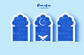 Ramadan Kareem Greeting card with Symbol of Islam - Crescent Moon The holy book of the Koran on the stand Paper cut Mosque Window. Holy month of muslim. Islamic festival. Blue.
