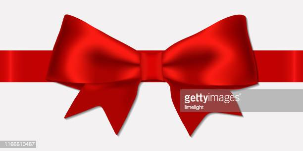 realistic decorative shiny satin red ribbon bow, isolated on white background. - tied bow stock illustrations