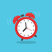 Red alarm clock isolated on blue background.