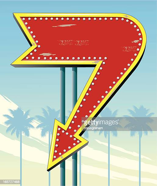 Red and gold downward arrow sign and palm trees
