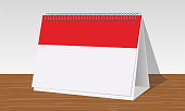 red and white calendar on wooden desk