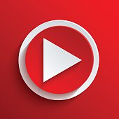 A red and white play button on a red background