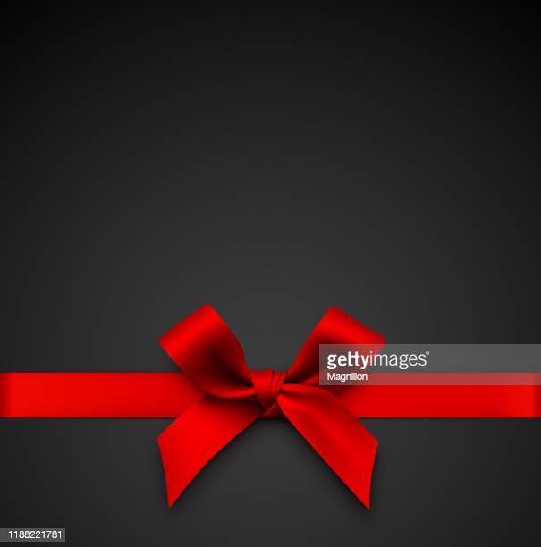 red gift bow with ribbon on a black background - tied bow stock illustrations
