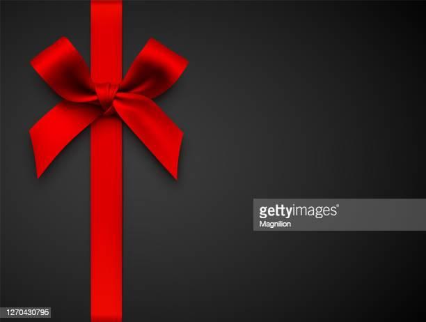rote geschenkschleife mit band auf schwarzem hintergrund - geschenk stock-grafiken, -clipart, -cartoons und -symbole
