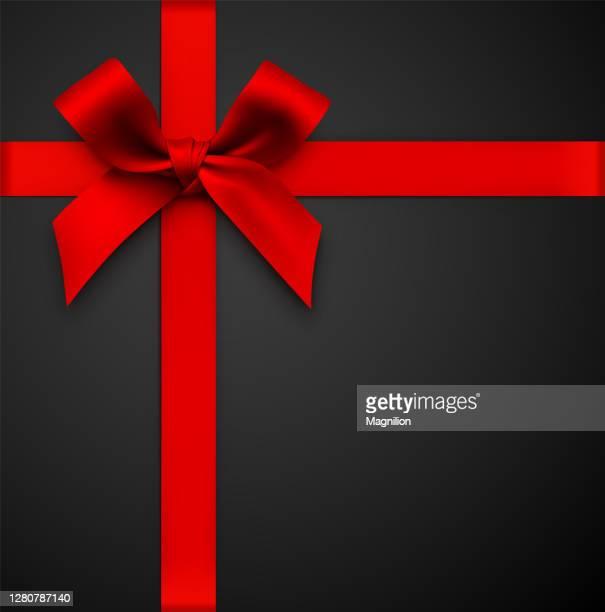 rote geschenkschleife mit band auf schwarzem hintergrund - vertikal stock-grafiken, -clipart, -cartoons und -symbole
