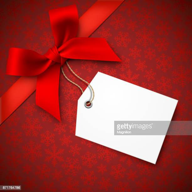 red holiday background with red bow and tag - gift stock illustrations