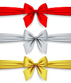 Red, silver and gold ribbons with bow isolated on white background