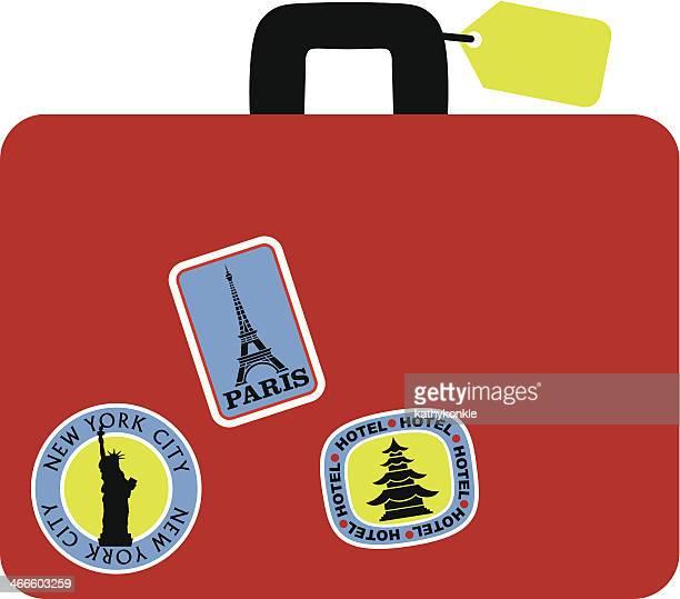 Valise rouge avec étiquettes à bagages