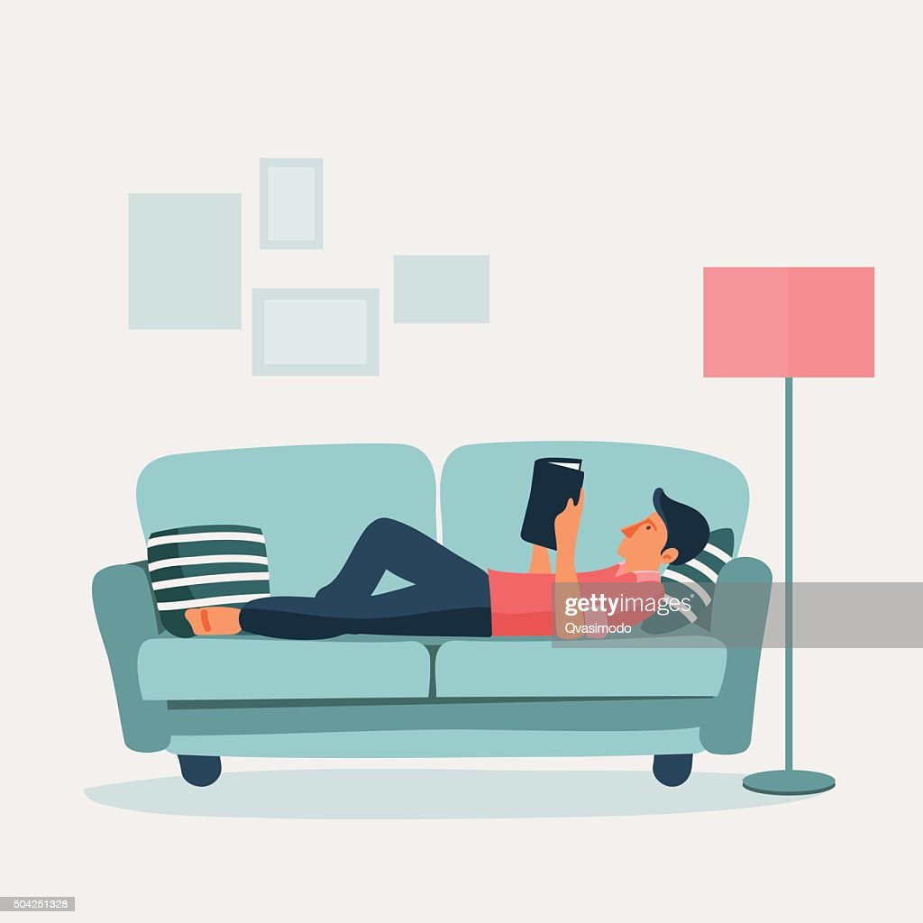Relaxed young man reading a book on a sofa
