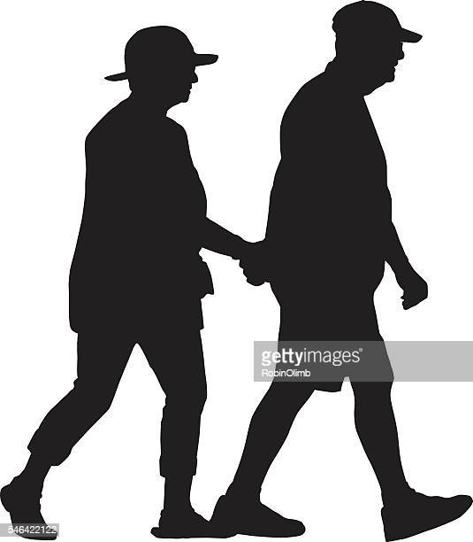 Retired Couple Walking Holding Hands