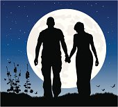 Romantic couple at night in silhouette against the moon.