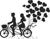Romantic couple man and woman on a date driving tandem bike with heart balloons silhouette
