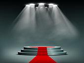 Round podium illuminated by searchlights
