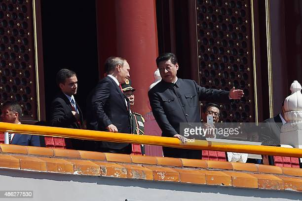 Russian President Vladimir Putin speaks with Chinese President Xi Jinping on top of Tiananmen Gate to watch a military parade to commemorate the 70th...