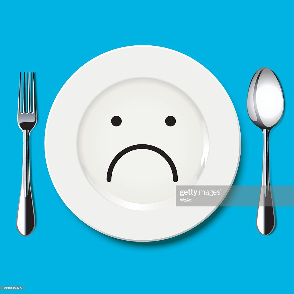 Sad face draw on white plate with spoon and fork