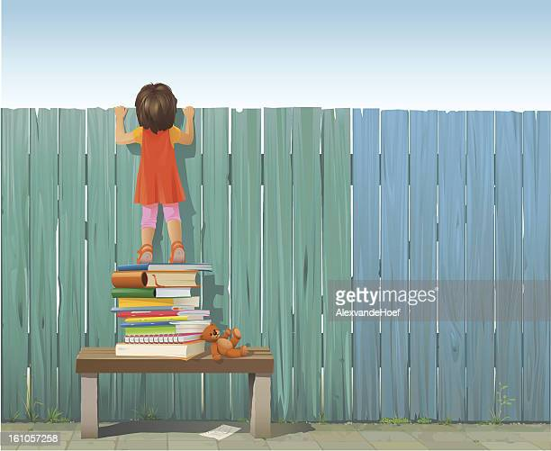 Schoolgirl on pile of books looking over fence