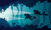 Scuba diver, lantern, coral reef, underwater cave and sea.