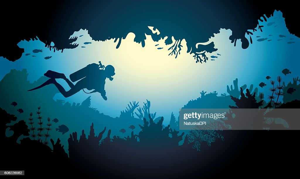 Sea cave with diver and coral reef.